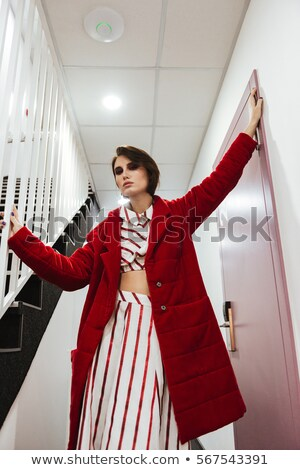 Woman in red coat standing and posing at hallway Stock photo © deandrobot