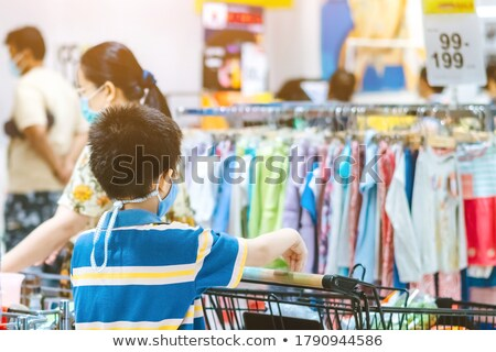 Back view of young boy in shopping trolley Stock photo © deandrobot