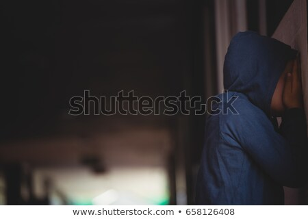 Side view of sad boy covering his face with hands while leaning on wall Stock photo © wavebreak_media
