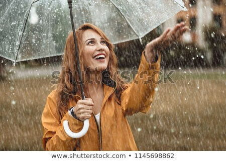 Girl holds hand out to catch rain Stock photo © IS2