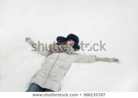Smiling woman lays in snow portrait Stock photo © IS2