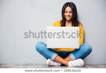 Fiatal nő ül padló lábak keresztbe kanapé póló Stock fotó © IS2