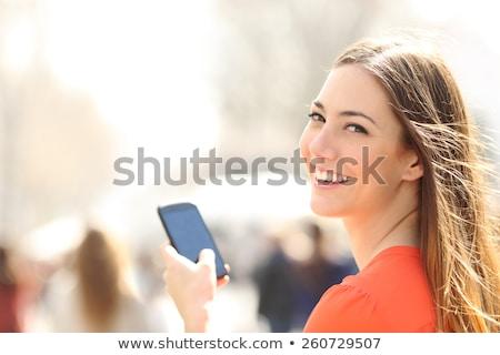 tinilány · magasra · tart · mobiltelefon · mosolyog · lány · mosoly - stock fotó © monkey_business