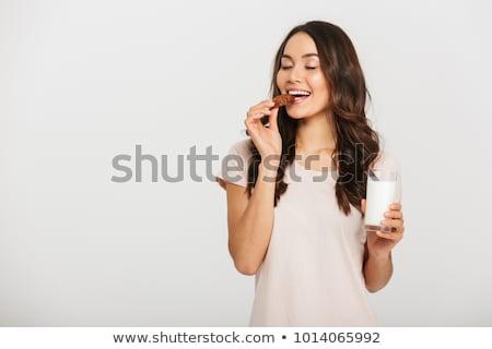 Portret tevreden jonge vrouw eten gebak geïsoleerd Stockfoto © deandrobot