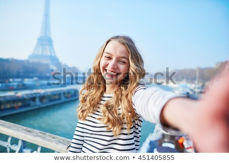 Beautiful young girl taking funny selfie with her mobile phone near the Eiffel tower. stock photo © artfotodima