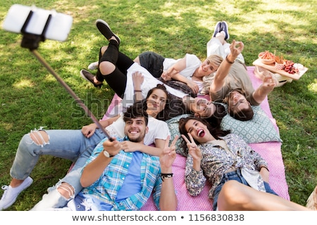 friends taking picture by selfie stick at picnic Stock photo © dolgachov