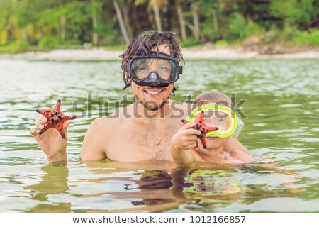 Father and son show a red starfish against the backdrop of the sea Stock photo © galitskaya