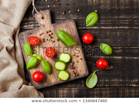 Organic Tomatoes and cucumbers with basil and linen towel on chopping board on wooden kitchen table. Stock photo © DenisMArt