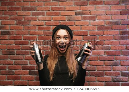 Image of delighted hip hop girl 20s, standing against brick wall Stock photo © deandrobot