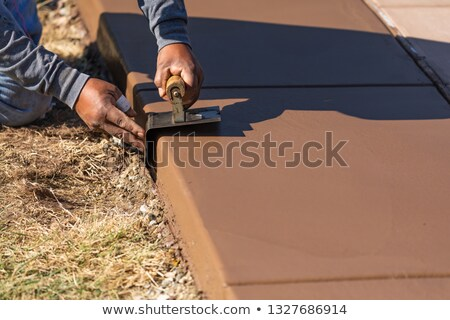 Construction Worker Smoothing Wet Cement With Curb Tool Stock photo © feverpitch
