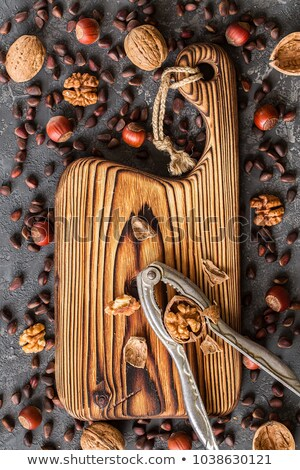 Old cutting board  and different nuts on stone table. Stock photo © Valeriy