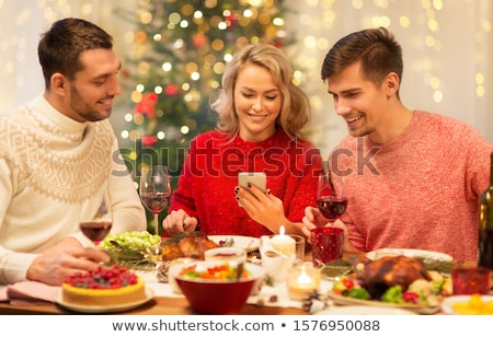 friends with smartphones having christmas dinner stock photo © dolgachov