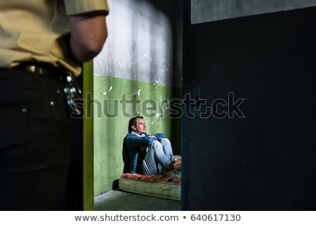 Young male prisoner sitting alone in an obsolete prison cell Stock photo © Kzenon