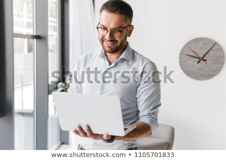 Handsome office man wearing white shirt expressing success while Stock photo © deandrobot