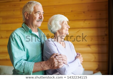 Affectionate contemporary casual spouses looking through window Stock photo © pressmaster