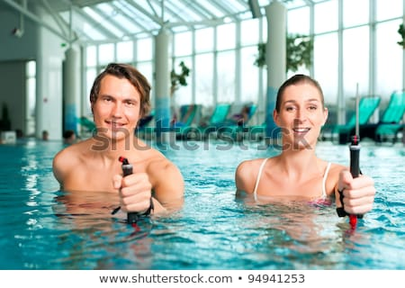 Couple exercising with nordic walk stick in swimming pool Stock photo © Kzenon