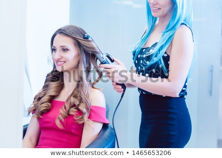 Woman customer getting curly hair in parlor of hip hairdresser Stock photo © Kzenon