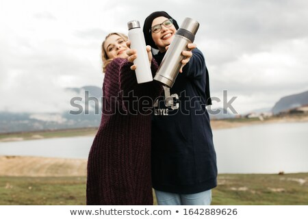 Young female in muslim hijab having refreshing drink outdoors Stock photo © pressmaster