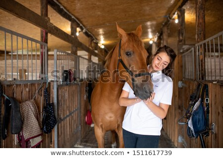 Young active woman in white shirt standing inside stable by purebred racehorse Stock photo © pressmaster