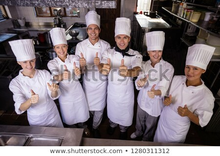 Group of chefs showing thumbs up sign in kitchen at hotel Stock photo © wavebreak_media