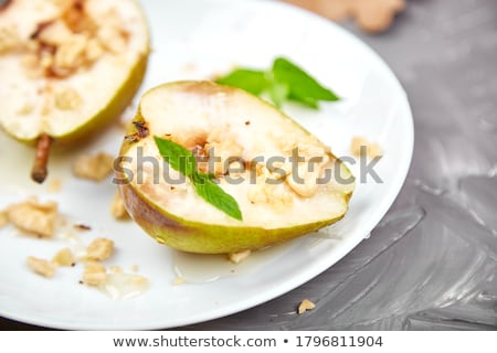 Tasty roast pears with honey and walnuts on grey background table. Stock photo © Illia