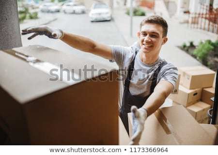 Smiling Young Male Relocation Worker Carrying Cardboard Boxes Stock photo © AndreyPopov