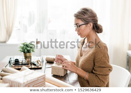 Serious young casual woman binding thread on top pf wrapped and packed box Stock photo © pressmaster