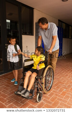 Front view of a cute mixed-race disabled schoolboy in wheelchair with handsome Caucasian male teache Stock photo © wavebreak_media