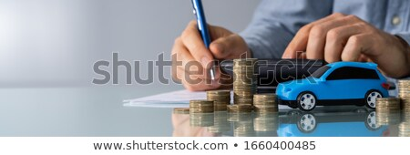 Red Car In Front Of Businessman Calculating Loan Stock photo © AndreyPopov