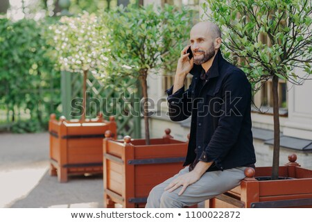 Portrait of cheerful middle aged bearded male speaks with someone via cell phone, has appealing look Stock photo © vkstudio