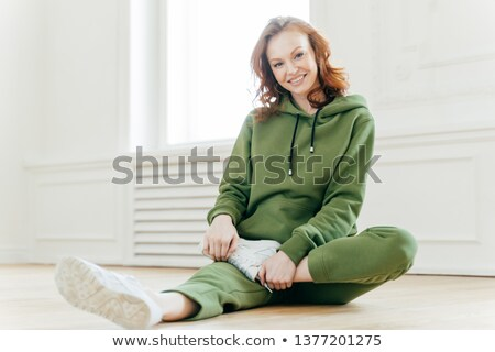 Photo of happy red haired woman in sweatsuit, white sneakers, takes rest after workout, sits on floo Stock photo © vkstudio