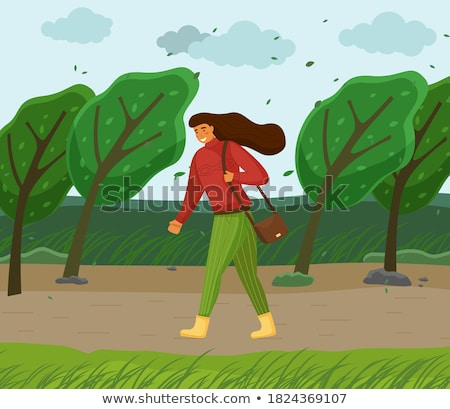 Young Woman Walking in Windy Weather Through Park Stock photo © robuart