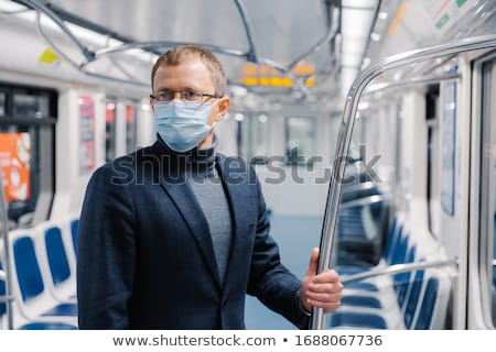 Male commuter poses in empty subway carriage, wears medical mask to prevent infected coronavirus at  Stock photo © vkstudio