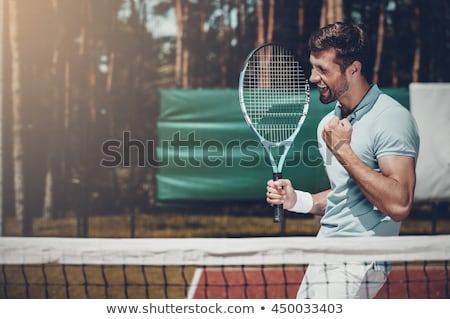 Image of athletic young man holding rackets while playing tennis Stock photo © deandrobot