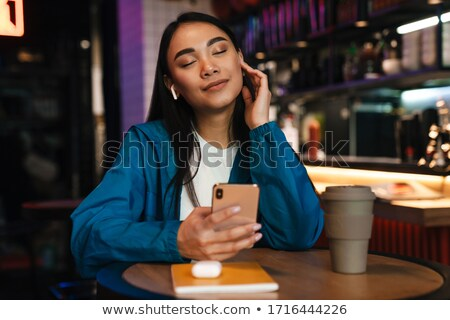 Photo of nice smiling woman using earphones and cellphone Stock photo © deandrobot
