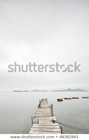 Stok fotoğraf: Looking Over A Desolate Peer And A Boat