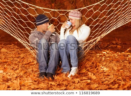 Young couple sitting in a hammock with drinks Stock photo © photography33