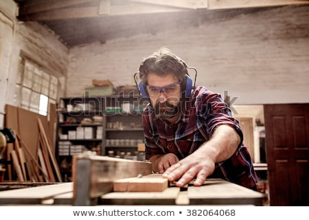 Man using a saw to cut a wooden plank Stock photo © photography33