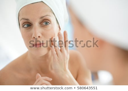 portrait of woman putting cream on face Stock photo © phbcz