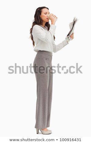 Attractive businesswoman reading a newspaper holding a coffee against white background stock photo © wavebreak_media