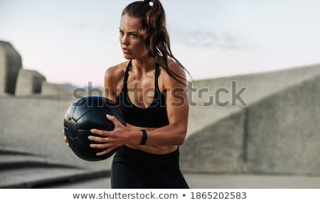 Fitness routine using exercise ball by athletic young woman stock photo © darrinhenry