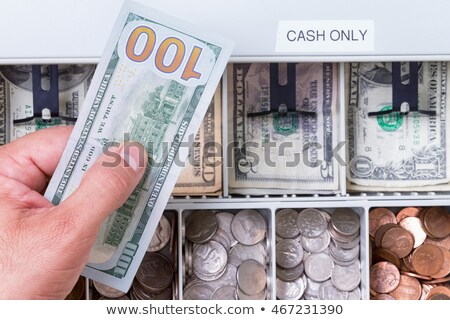 Сток-фото: Hand Holding Hundred Dollar Bill Over Cash Drawer