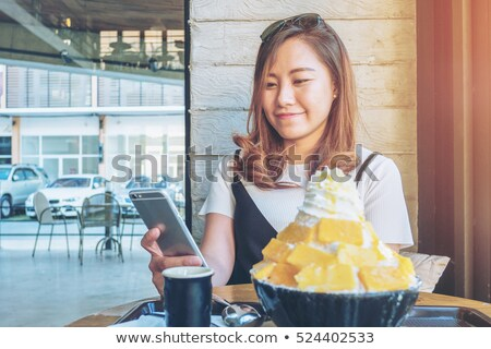 cute young woman eating and using cell phone in cafe stock photo © deandrobot