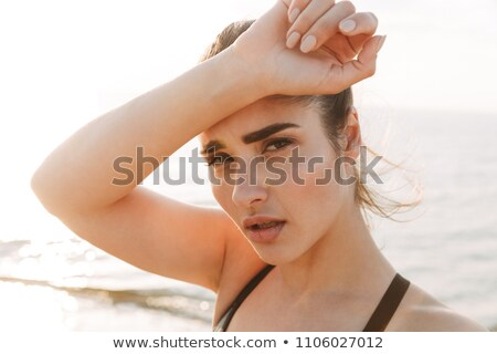 Close up portrait of a tired young sportswoman wiping forehead Stock photo © deandrobot