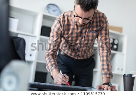 A man in the office is standing near the table and draws a marker on the magnetic board. Stock photo © Traimak