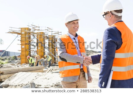 Architect and engineer or supervisor shaking hands on the construction site Stock photo © Kzenon