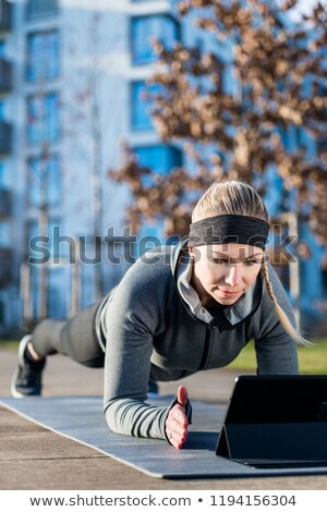 Young woman watching a motivational video while exercising outdoors Stock photo © Kzenon