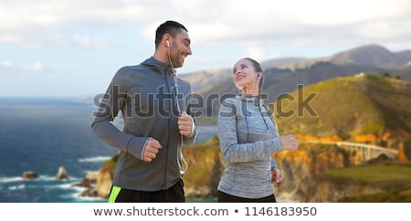 happy man in earphones running over big sur coast Stock photo © dolgachov
