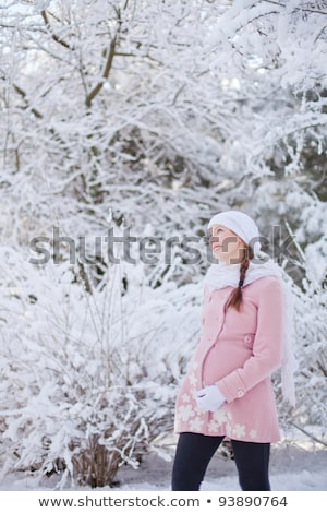 young happy pregnant woman in snowy forest stock photo © lopolo
