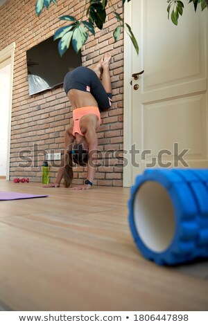 A woman stands upside down in the living room and meditates Stock photo © galitskaya